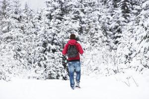 ung man som vandrar i vinterskoglandskap foto