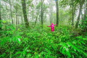 unga kvinnor som står i regnskogen foto