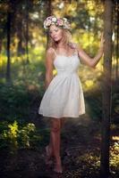 vacker blond ung kvinna i skogen foto