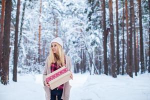 flicka som håller en julklapp i vinterskogen foto