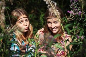 två glada unga flickor i en sommarskog