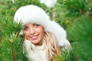 kvinna i hatt, vantar, halsdukar, tröjor i vinterskogen foto
