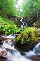 vattenfall i den karpatiska höstskogen. vatten med motion blu foto
