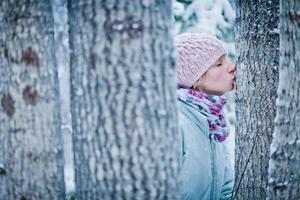 härlig tjej som kysser ett träd i skogen (ekologikoncept) foto