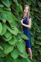 vacker blondin poserar i trädgården foto