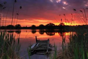 gammal fiskebro på sjön vid solnedgången foto