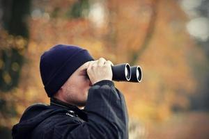 man tittar genom kikare
