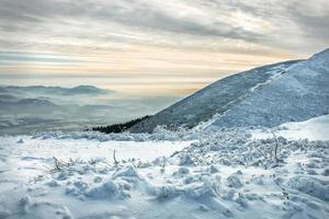 vacker bergsutsikt på vintern under solnedgångshimlen. foto