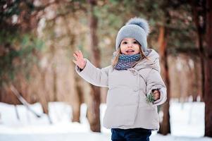 söt flicka på mysig promenad i snöig vinter skog foto
