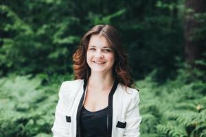 porträtt av ung glad skönhet flicka i jacka i skogen