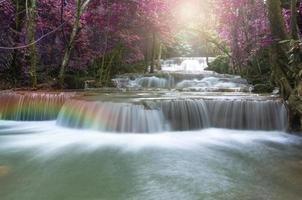 vackert vattenfall i mjukt fokus med regnbågen i skogen foto