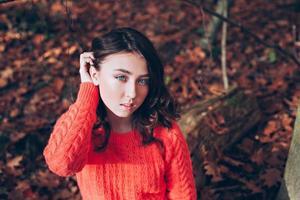 porträtt av ung flicka med blå ögon i höstskog