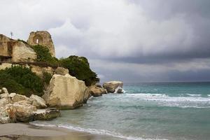 klippa och torn på stranden i Torre dell'orso