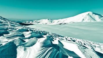 figurvind på en snöig bergssida foto