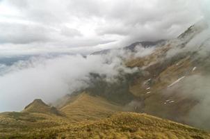 bergskedja, täckt av moln.