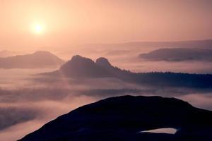 drömmande dimmigt landskap. majestätiska berg skär belysning dimman.
