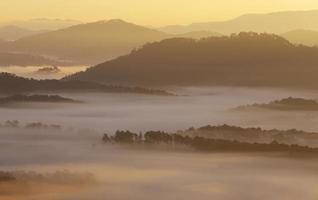 berg, dimma och solljus vid gryningen