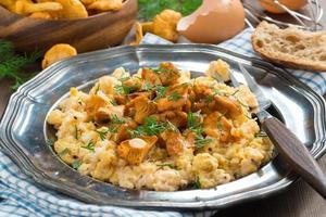 äggröra med kantareller och färsk dill på en tallrik foto