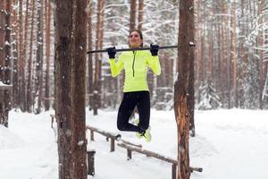 fit kvinna idrottsman utför pull ups i en bar. vinter- foto