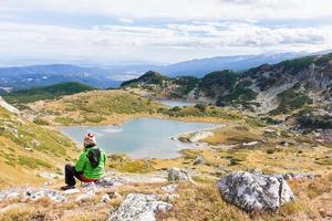 turist kvinna sitter ovanför sjöar. foto
