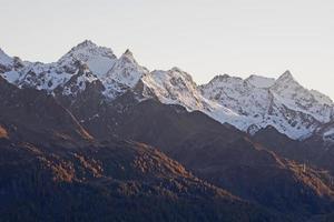 snötäckta bergstoppar på kvällsljuset