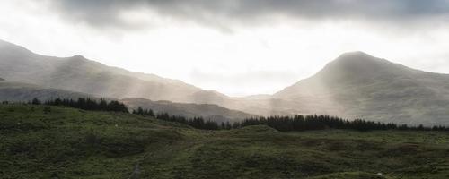 panorama landskap soluppgång över avlägsna dimmiga berg med solstrålar