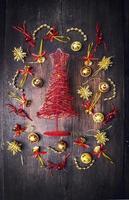 röd julgran med guldklockor, snöflingor, krans foto