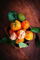 mandariner med blad på rustik träbakgrund foto