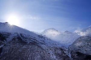 snöiga berg i dimma och himmel med sol