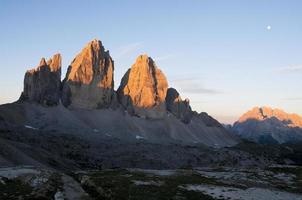 soluppgång och måne på tre cime di lavaredo