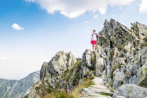 ung kvinna som klättrar höga berg foto