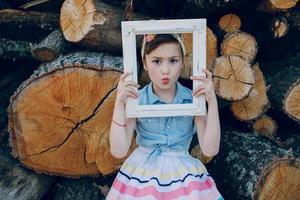 vacker liten flicka sitter på träd foto