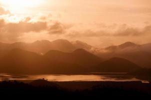 silhuett av bergen ovanför vattnet under orange molnlandskapsmoln foto