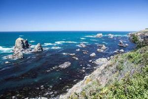Stilla havet och stenig kust foto