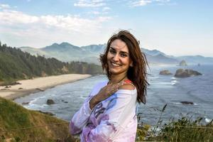 vacker leende ung kvinna vid havets kust foto