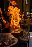 kock som grillar bbq med brännflamma i restaurangen foto