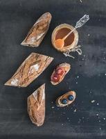 fransk baguette skuren i bitar, smörgåsar med röda druvor foto