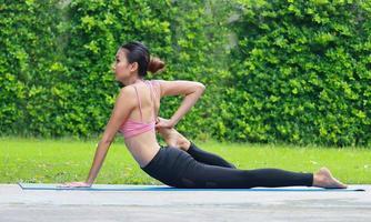 asiatisk kvinna som utövar yoga