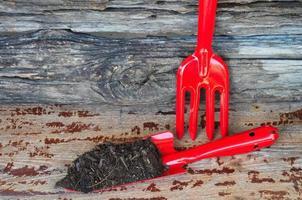 jord i spade och gaffel på träbakgrund. planteringskoncept foto