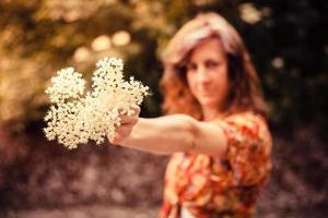 ung kvinna som håller ett gäng fläderblommor foto