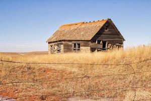 sönderfallande hus på ett fält foto