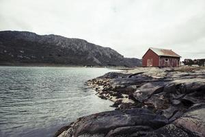 lofoten norge kust med rött hus på stenar foto