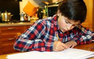 ung pojke skriver på sin anteckningsbok foto
