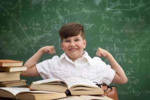 smart pojke som sitter vid skrivbordet och uttrycker kraften i kunskap foto