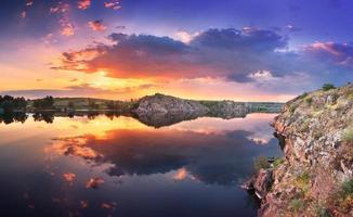 vacker sommarsolnedgång vid floden med färgglad himmel foto