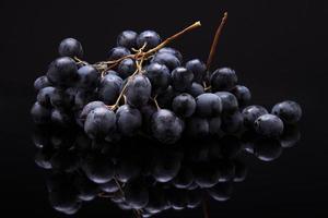 bild av svarta druvor på svart bakgrund med reflektion foto