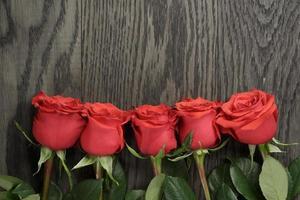 romantisk bakgrund med röda rosor på träbord foto