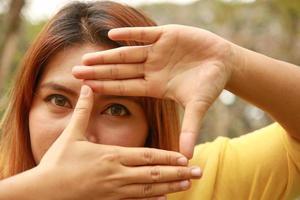 söt flicka gör ram med händerna foto