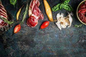 italienskt antipasto mellanmål med rökt kött, tomater och ciabattabröd foto