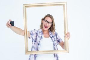 ganska nördig hipster tar selfie med smartphone foto